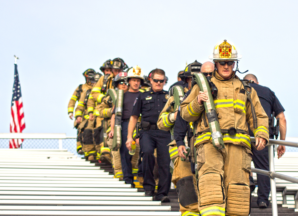 firefighter and police officers climbing stairs